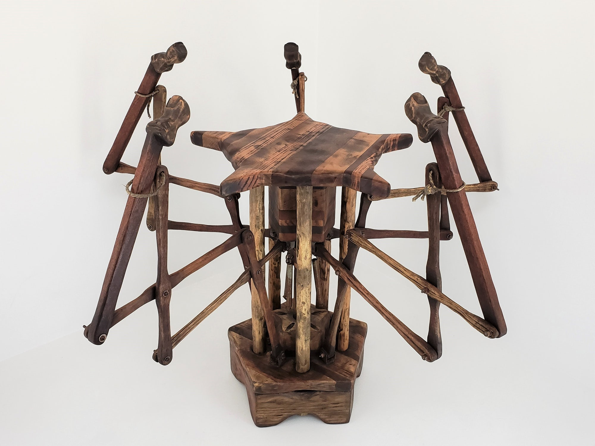 This stool points towards an occupant when the weight of a person rests on the seat. The five finger mechanisms extend and rise from beneath the seat when depressed. Once weight is released, springs pull the fingers down to their starting position and the